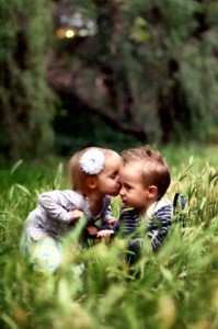 Ellie steals a kiss from Gray in the grass.